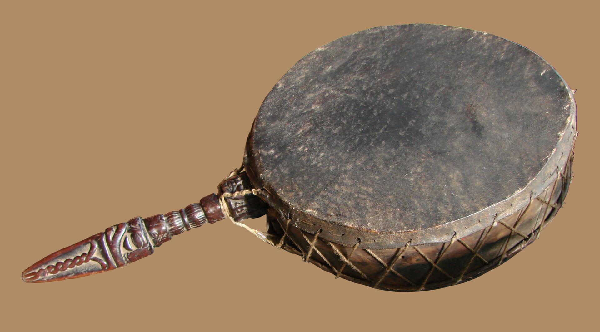 Tamburo tradizionale nepalese. Ha una parte di impugnatura che è rappresentata praticamente da una riproduzione di un phurba, un coltello rituale tradizionale. Fonte Wikipedia